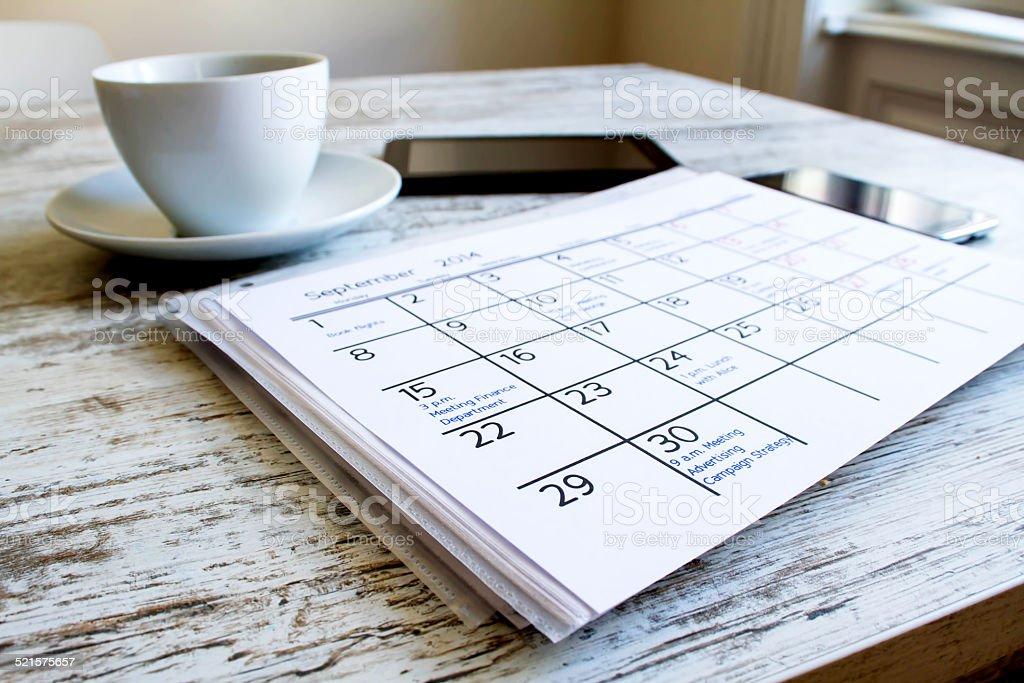 Checking monthly activities in the calendar stock photo