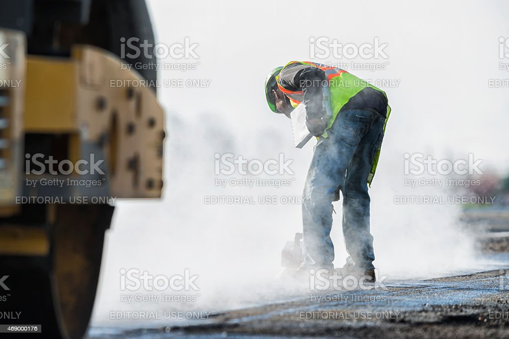QC checking of newly laid asphalt on highway stock photo