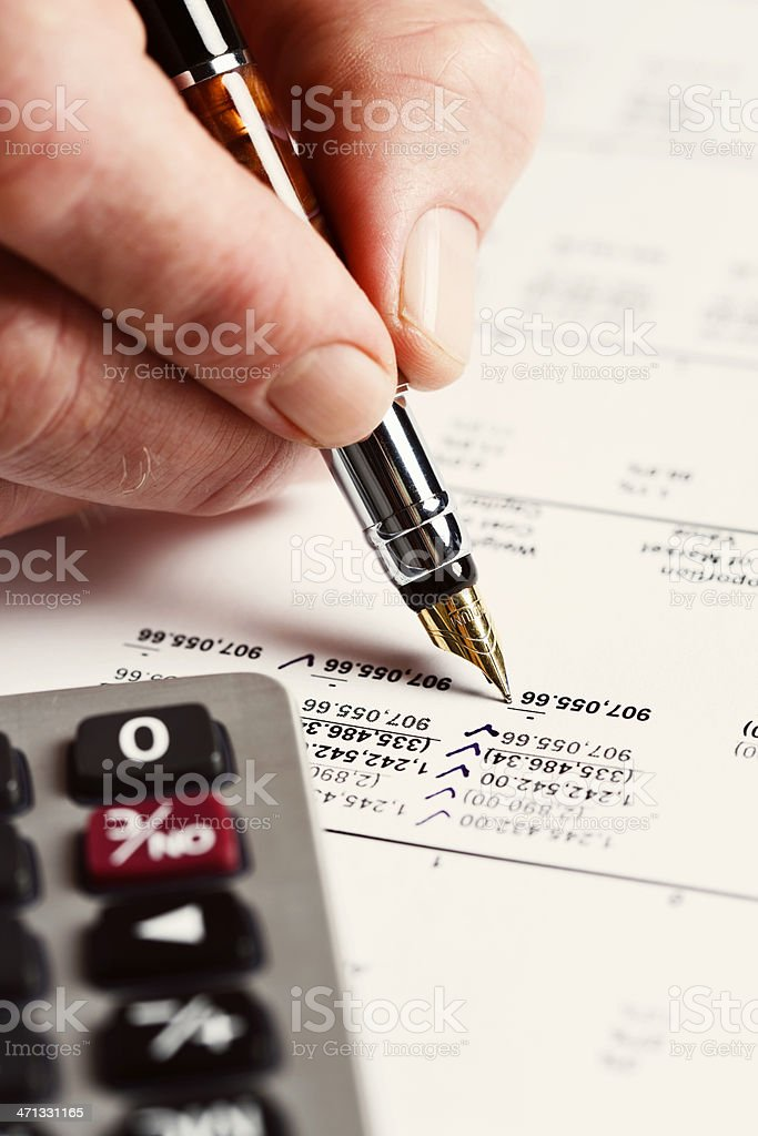 Checking off items with pen and calculator on financial printout royalty-free stock photo