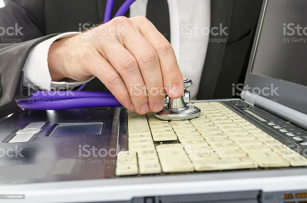 Checking old laptop with stethoscope royalty-free stock photo