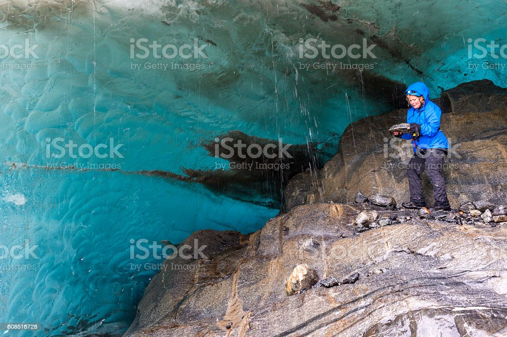Checking out rocks in an ice cave stock photo