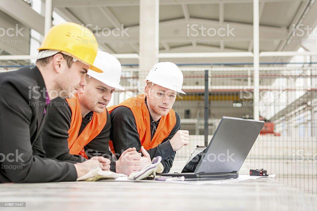Checking plans on laptop stock photo