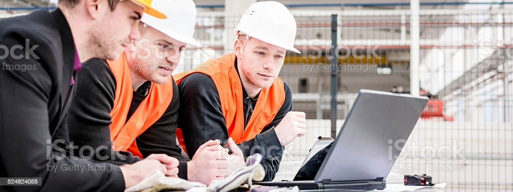 Checking Plans on Laptop stock photo