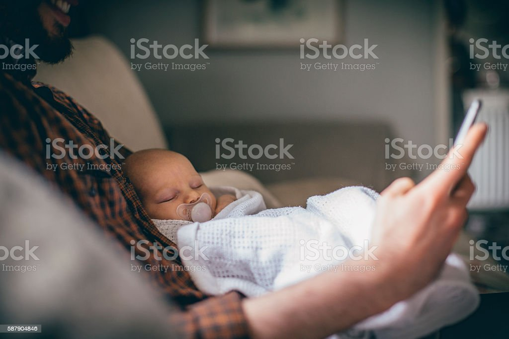 Checking social media while the baby sleeps stock photo