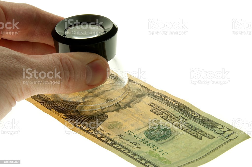 Checking the authenticity of a twenty dollar bill stock photo