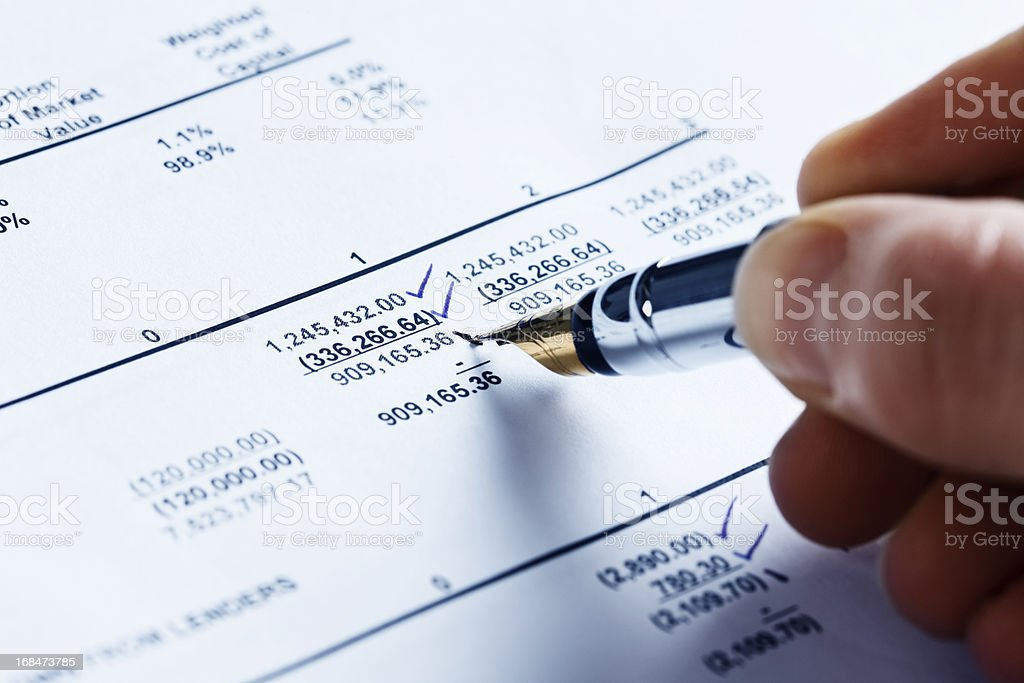 Checking the finances; man's hand marks off spreadsheet figures royalty-free stock photo