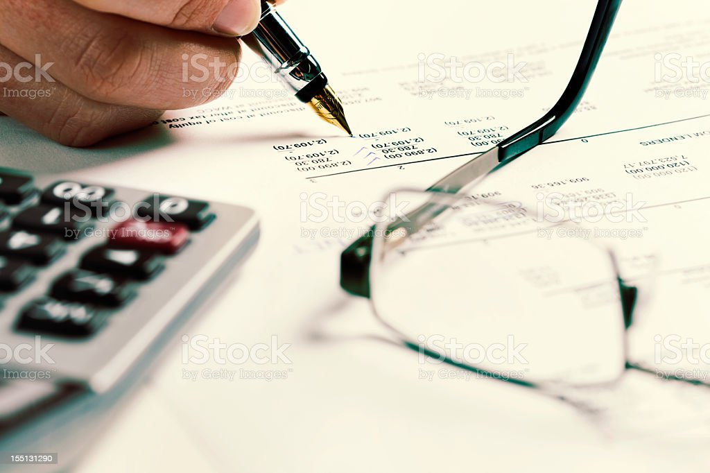Checking the finances: man's hand, pen, calculator and spreadsheet royalty-free stock photo