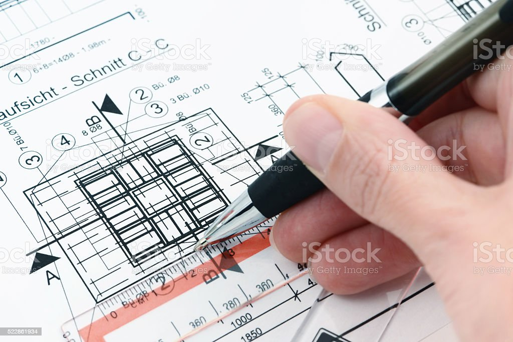 checking the measure on a blueprint plan of house building stock photo