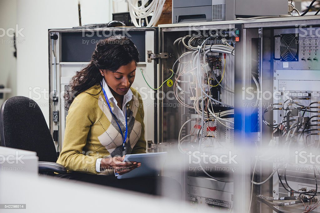 One woman checking on network servers using a digital tablet.