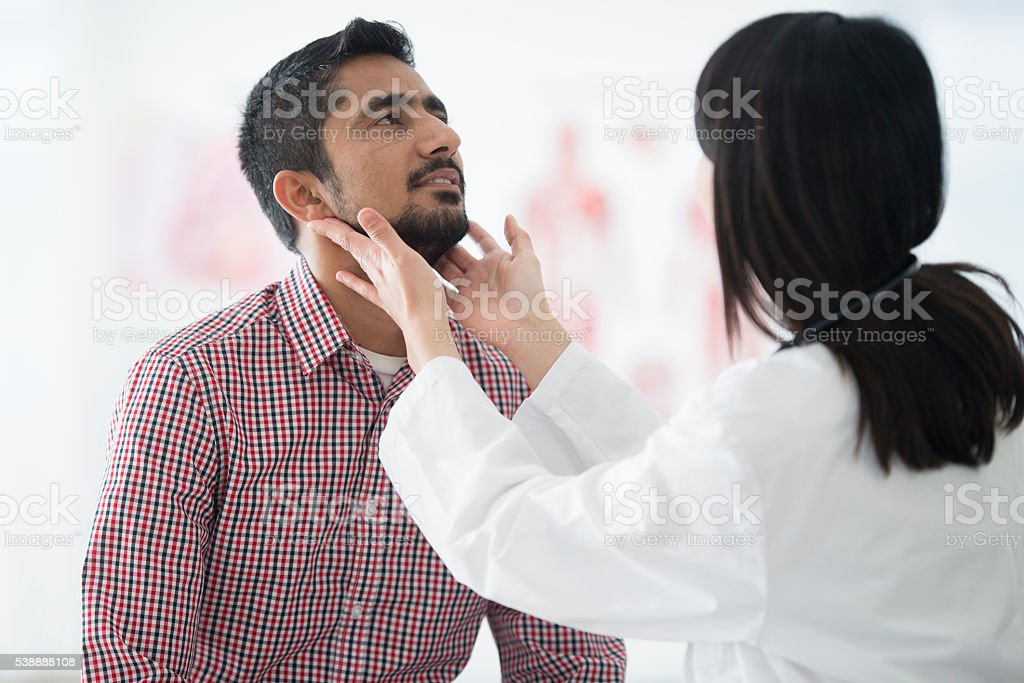 Checking the Size of a Man's Lymph Nodes stock photo