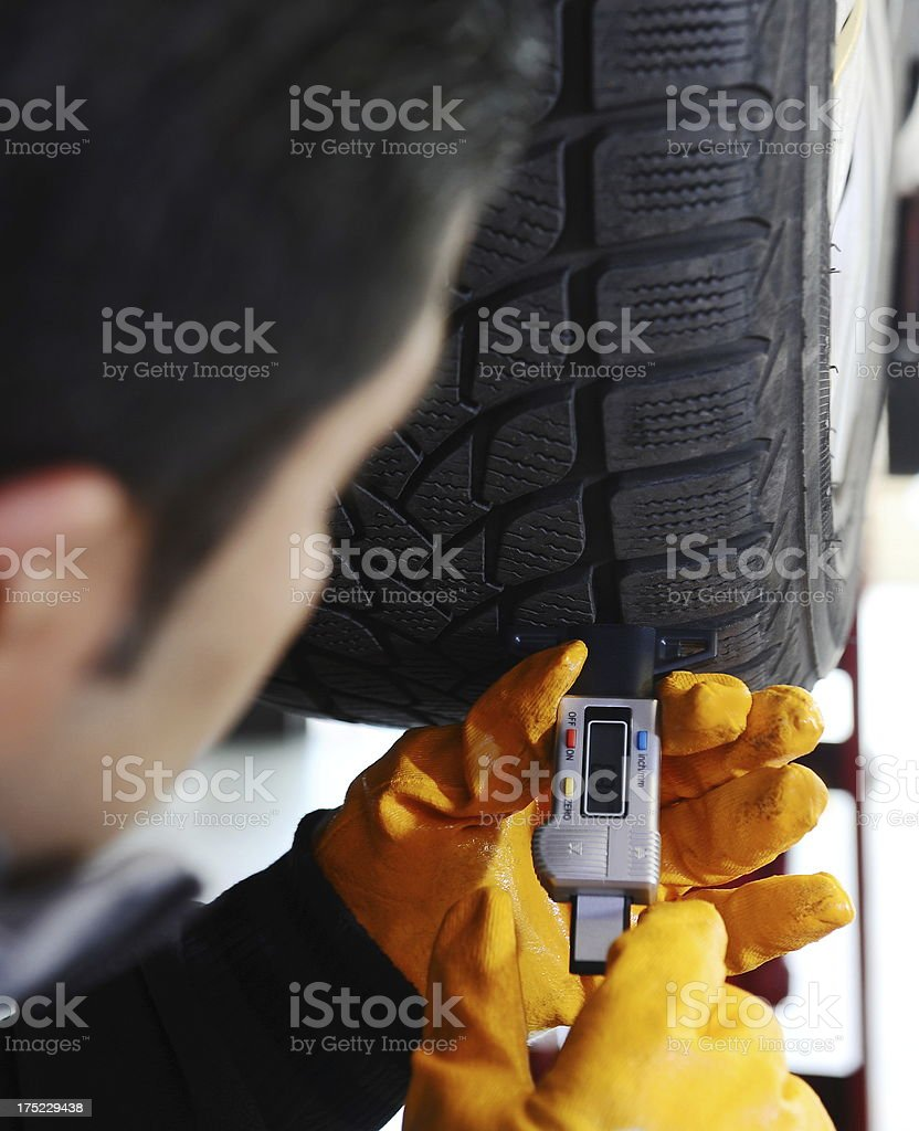 Checking tyres for right tread royalty-free stock photo