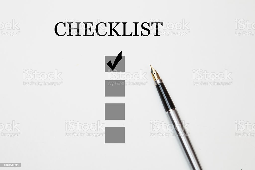 checklist with a ticked box and a pen stock photo