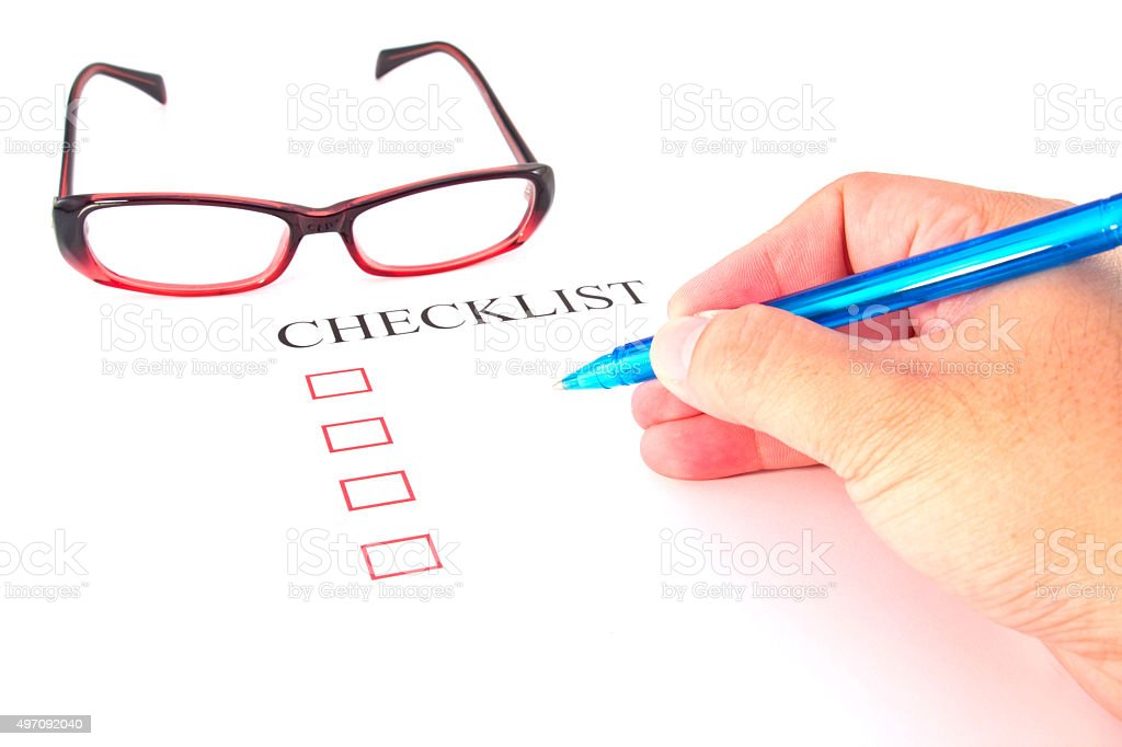 Checklist with pen, glasses and checked boxes. stock photo