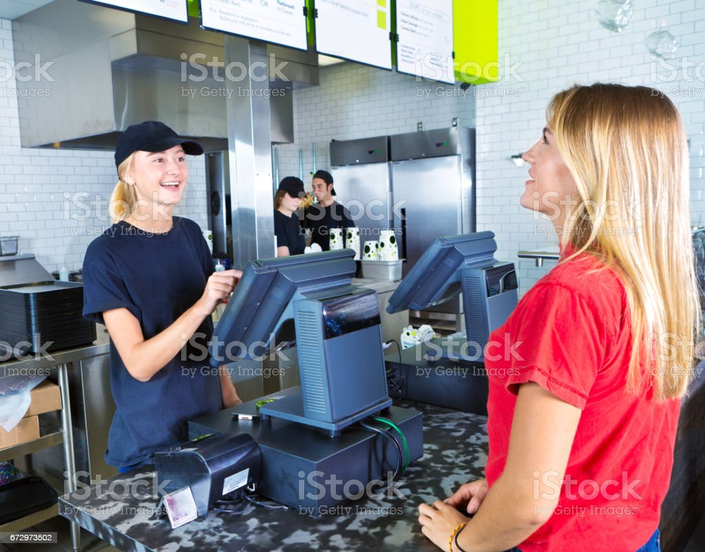 Checkout Server Serving Young Woman Customer Ordering at Fast Food Restaurant stock photo