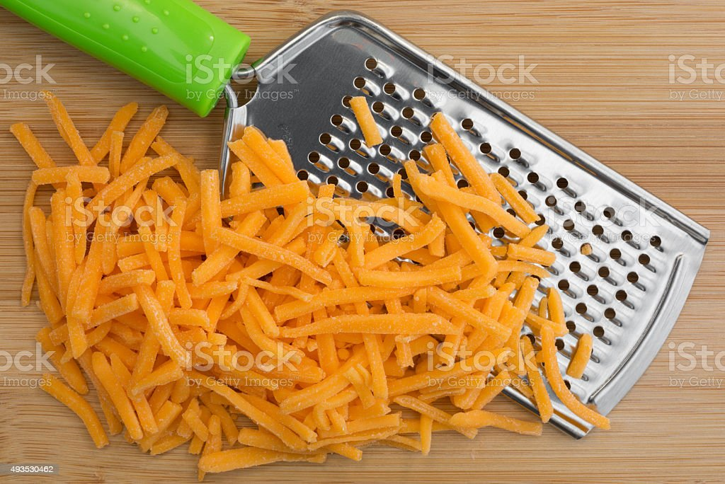 Cheddar cheese with grater on wood cutting board stock photo