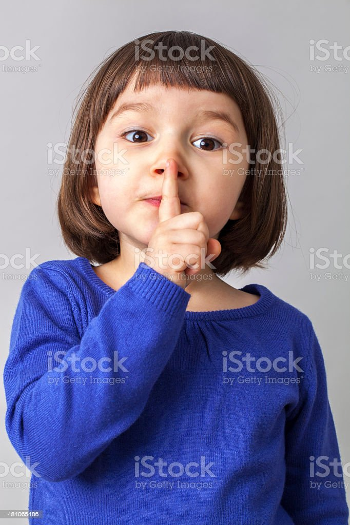 cheeky 4-year old girl expressing a secret stock photo