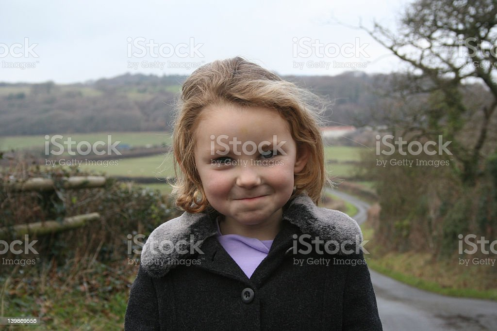 Cheeky looking girl on country walk stock photo
