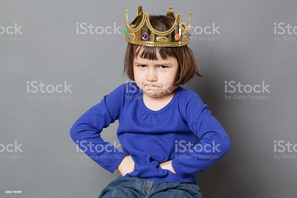 cheeky preschooler with attitude sulking with mollycoddled kid crown stock photo