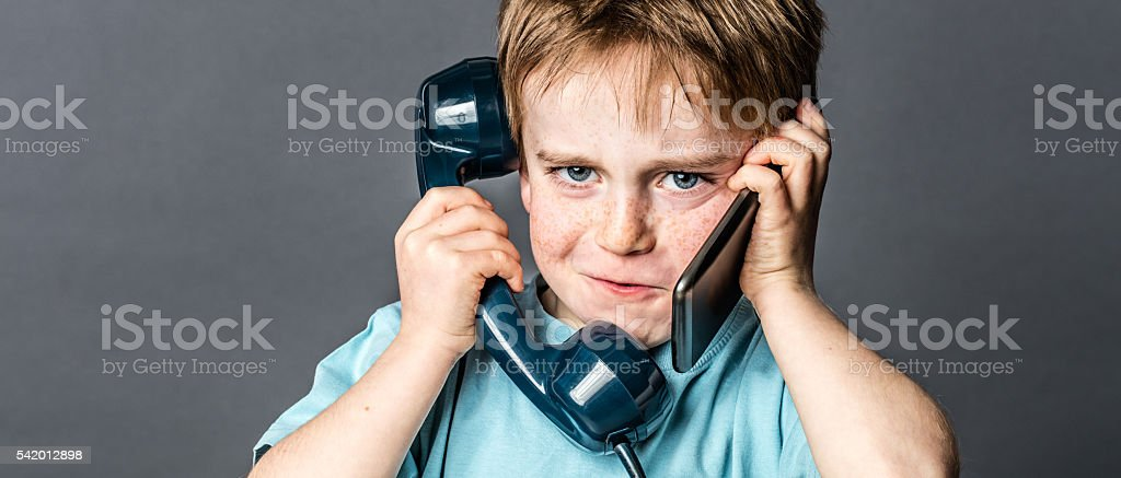 cheeky young boy talking on old telephone and new smartphone stock photo