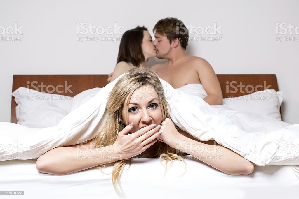 Cheeky young woman having a threesome in bed stock photo