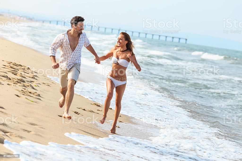 Cheerfful young couple running on beach stock photo