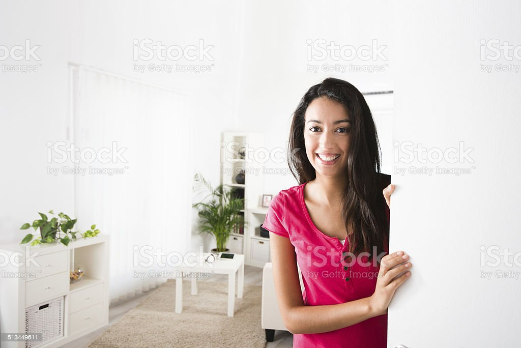 cheerfu young woman opening house frontdoor and inviting friends home stock photo