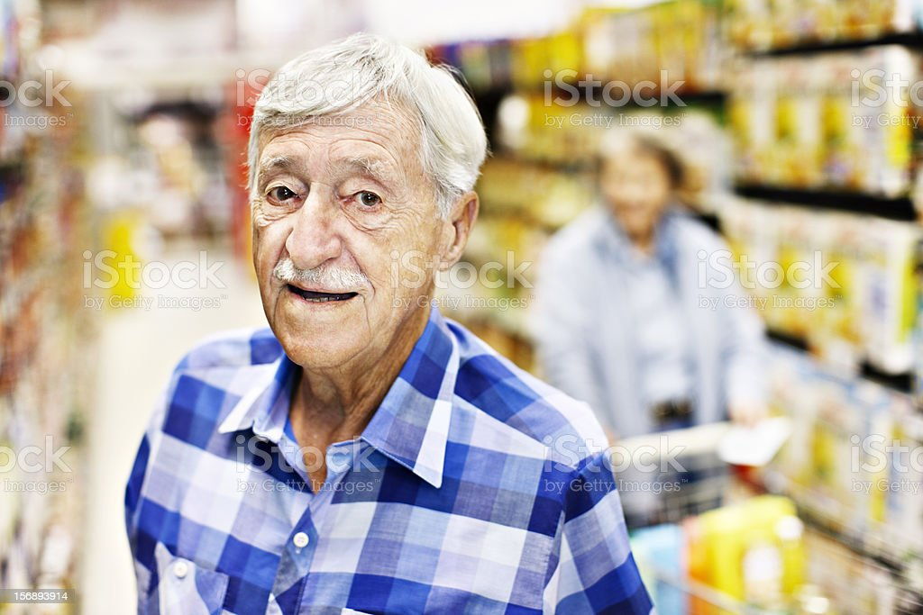 Cheerful 87 year old man shopping in supermarket stock photo