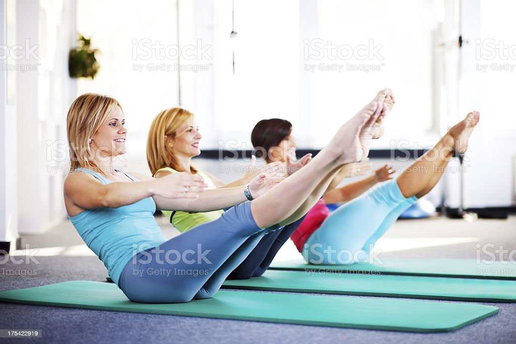 Cheerful adult women doing stretching exercises on Pilates class. stock photo