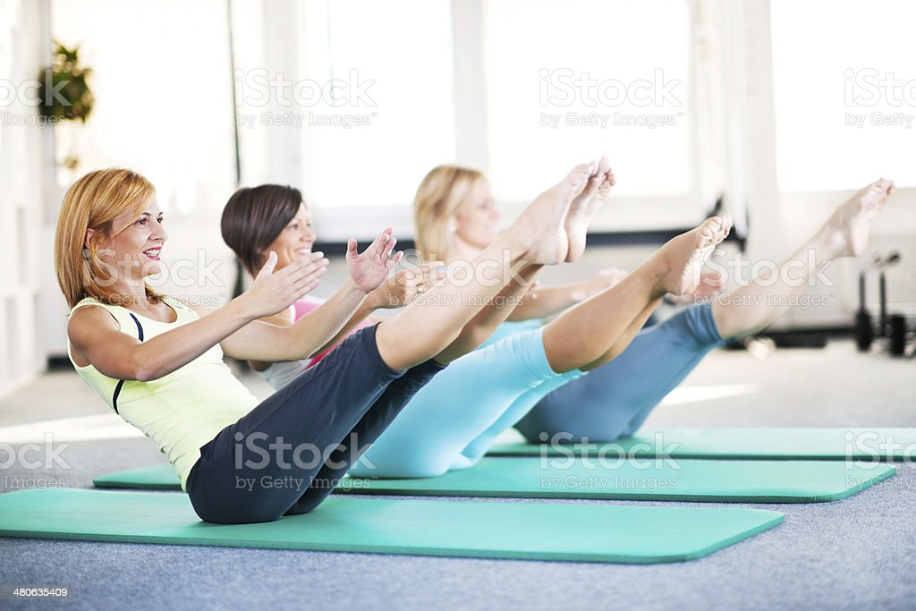 Cheerful adult women doing stretching exercises on Pilates class stock photo