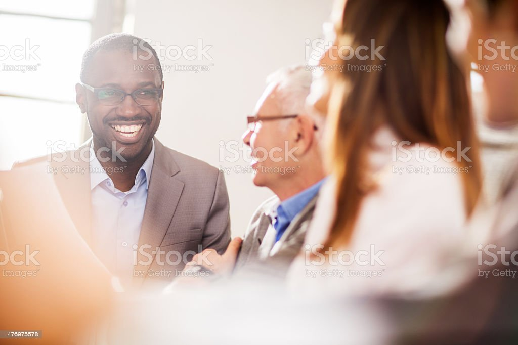 Cheerful African American businessman talking to his colleagues. stock photo
