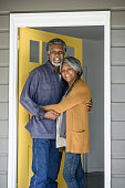Cheerful African American couple standing in doorway of house