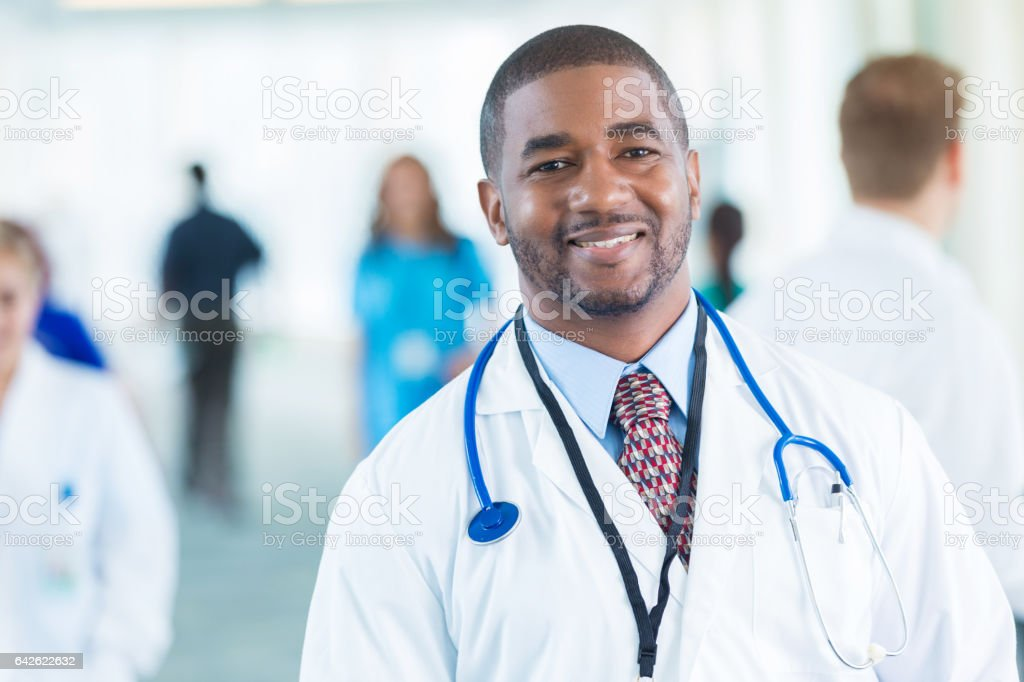 Cheerful African American doctor in busy hospital stock photo