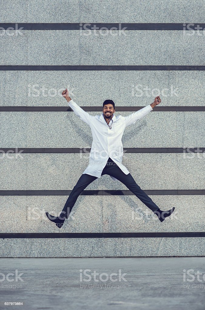 Cheerful African American doctor jumping against the wall. stock photo
