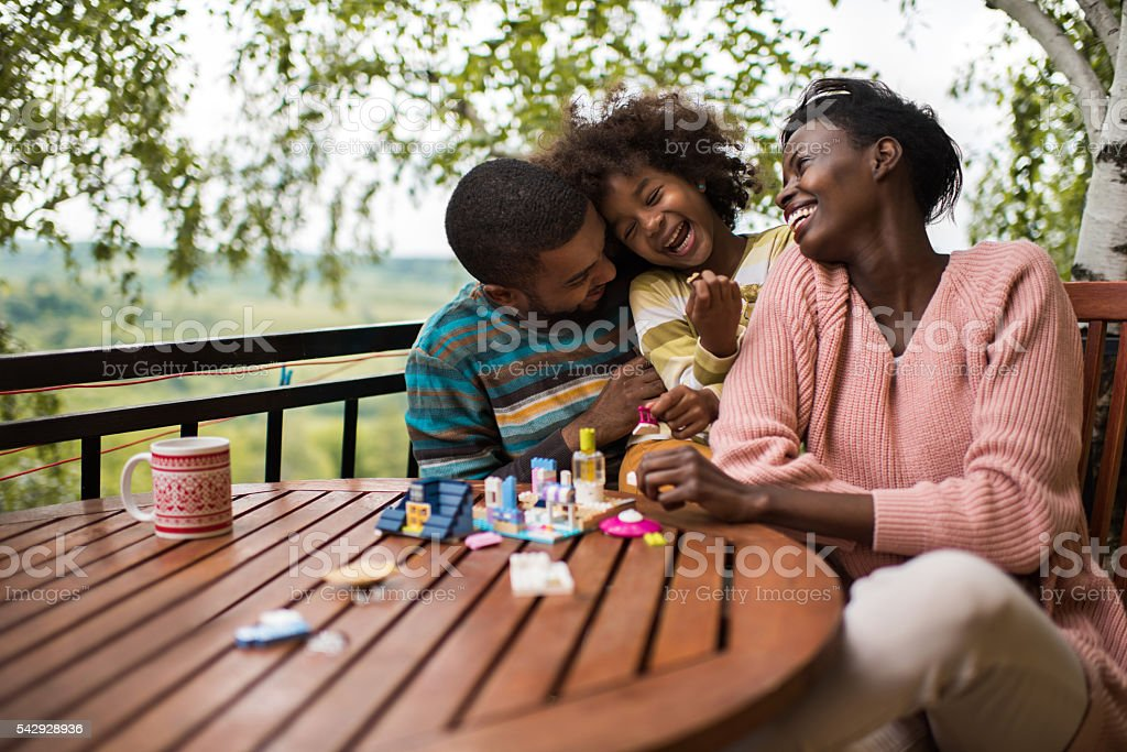 Cheerful African American family having fun on a terrace. stock photo