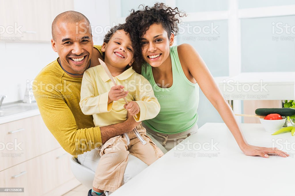 Cheerful African American family in the kitchen. stock photo