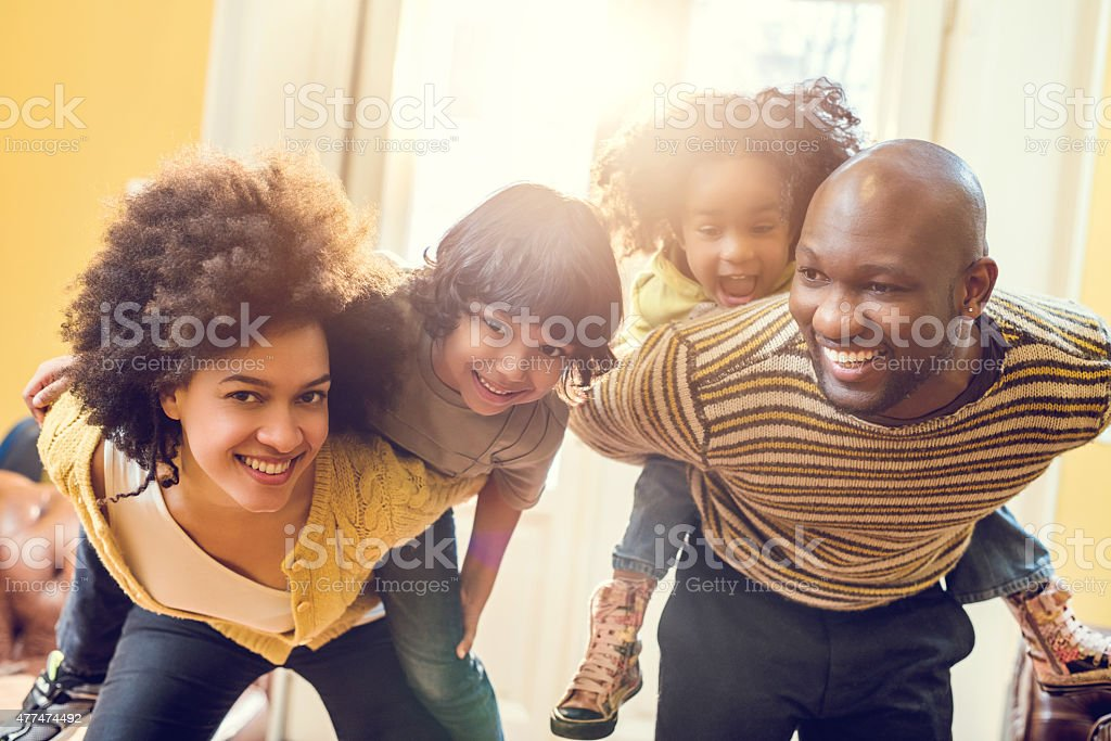 Cheerful African American family piggybacking at home. stock photo