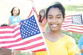 Cheerful African American girl waves American flag