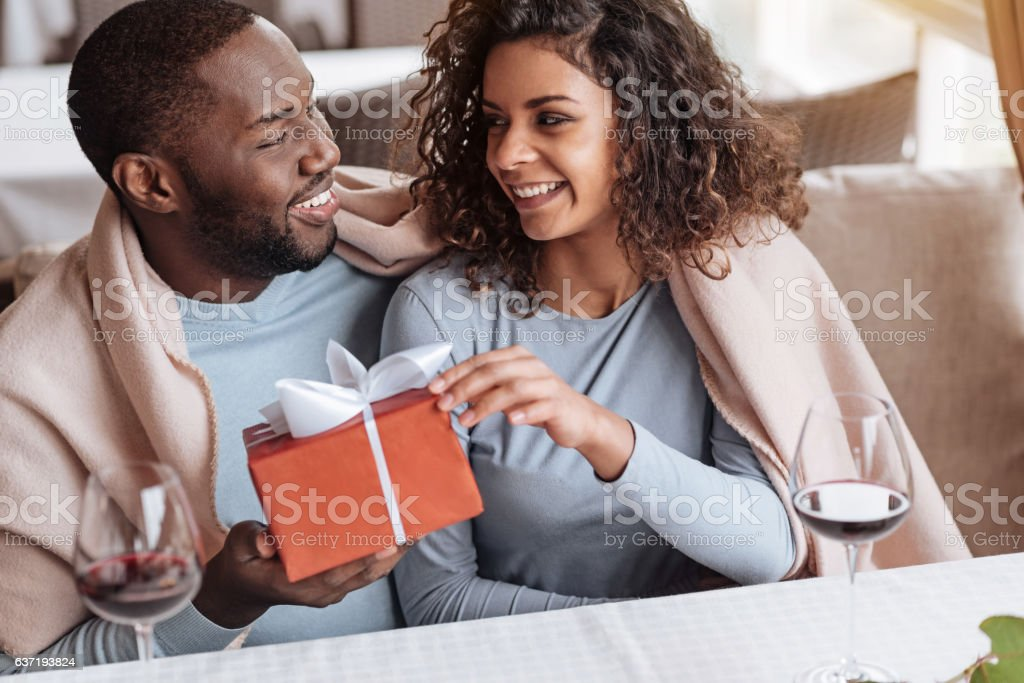 Cheerful African American man congratulating his girlfriend stock photo