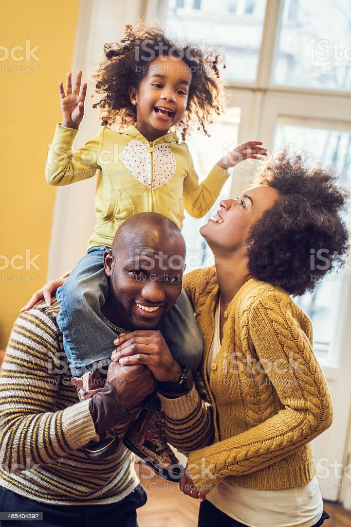 Cheerful African American parents having fun with their little daughter. stock photo