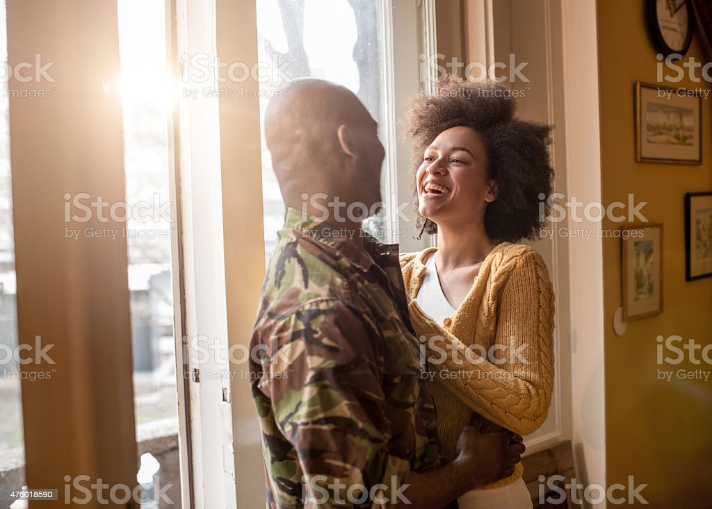 Cheerful African American woman talking to her military husband. stock photo