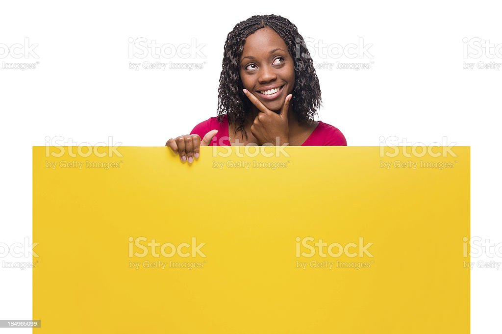 Cheerful african american woman thinking and holding a sign royalty-free stock photo