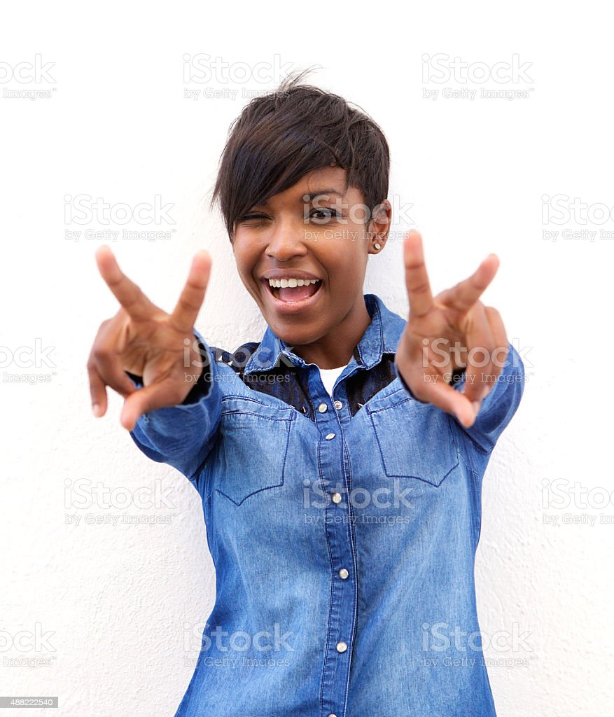 Cheerful african american woman with peace hand sign stock photo
