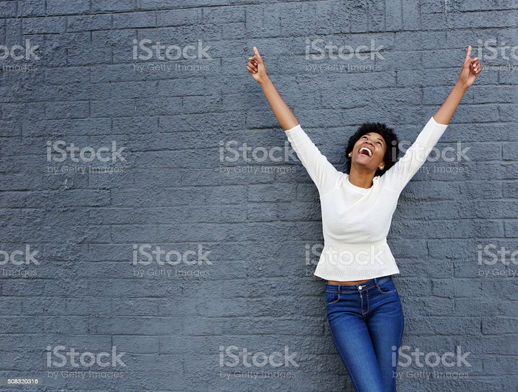 Cheerful african woman with hands raised pointing up stock photo