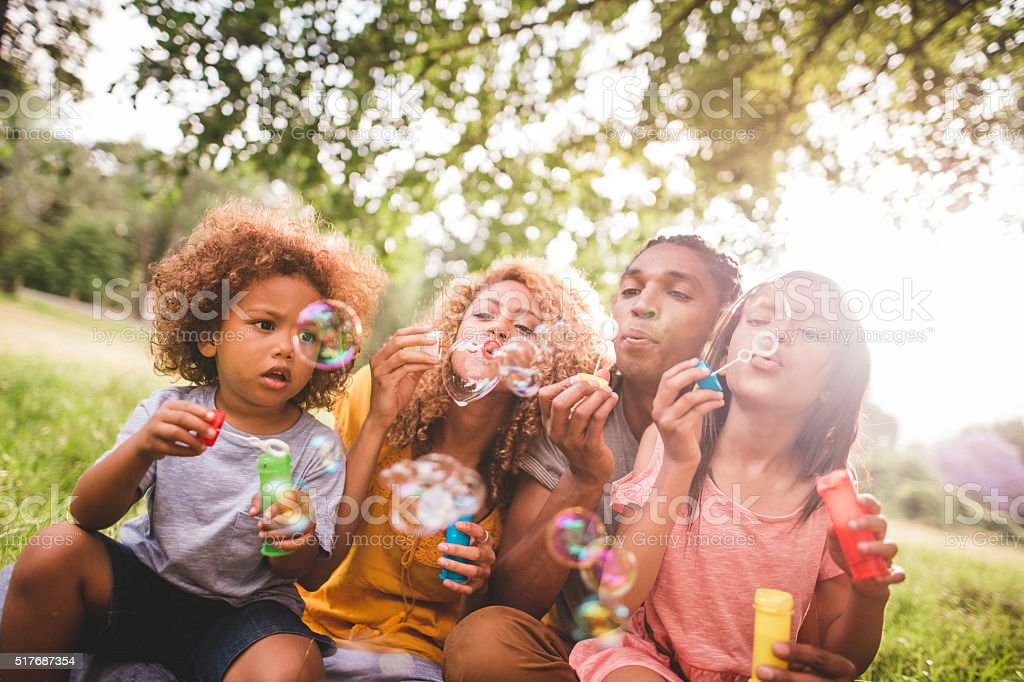 Cheerful african-american family bonding and blowing bubbles in stock photo