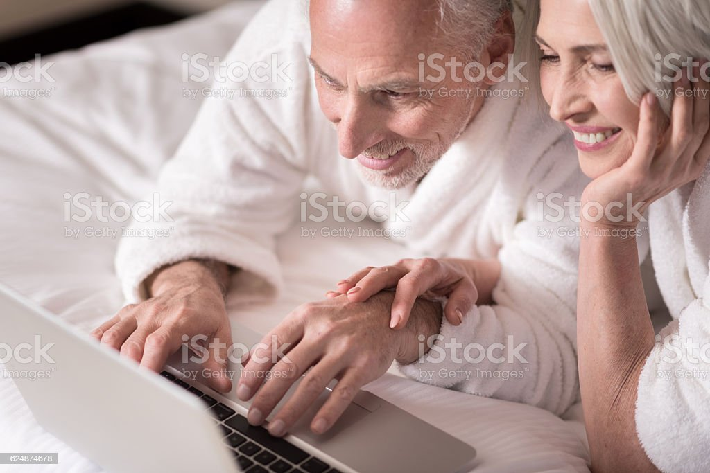 Cheerful aged couple lying on the bed at home stock photo