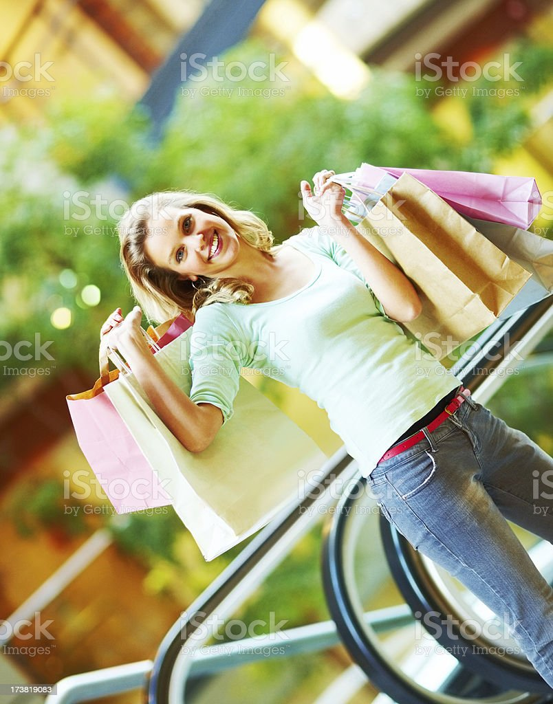 Cheerful and attractive young woman holding shopping bags royalty-free stock photo