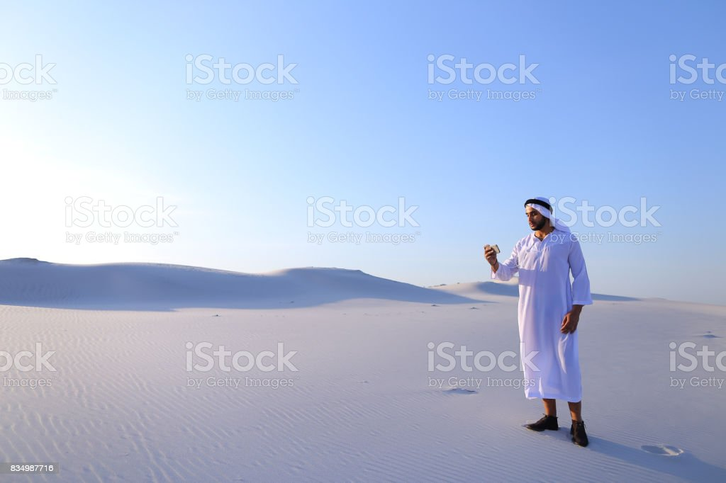 Cheerful Arab male tourist calls friend on Skype by cell and sho stock photo
