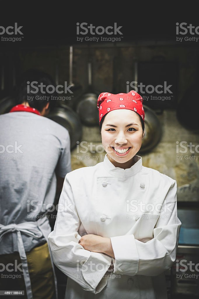 Cheerful Asian Female Cook in the Kitchen stock photo