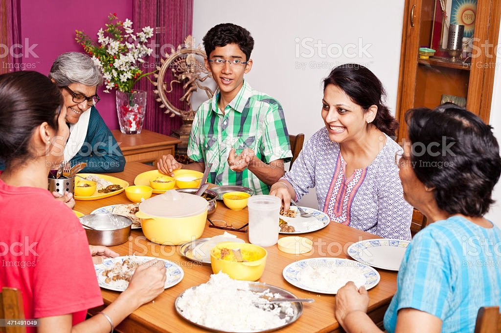 Cheerful Asian Indian Family Enjoying Meal Together stock photo
