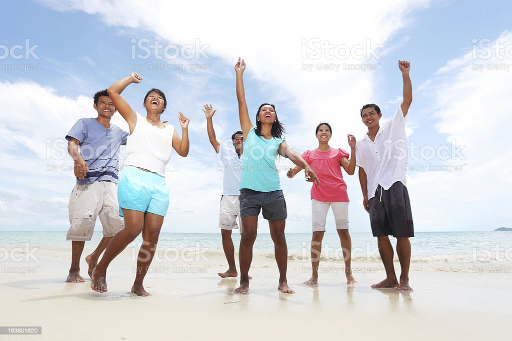 Cheerful asian people dancing on the beach. royalty-free stock photo